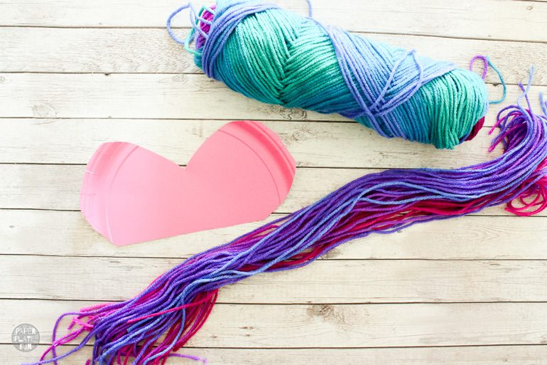 Cut long pieces of yarn to create a boho heart wall hanging.