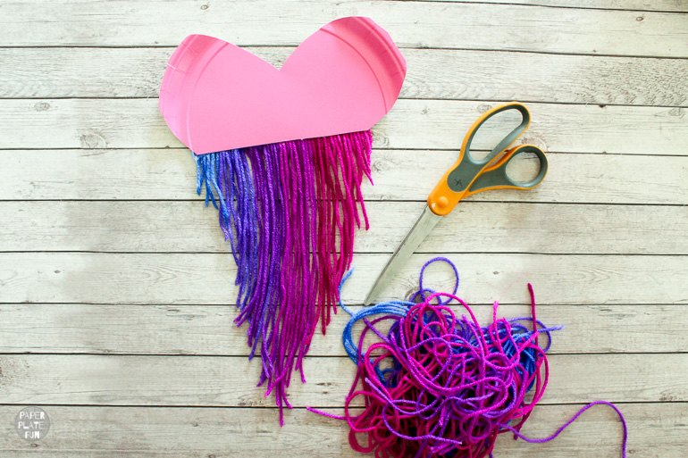 Cut the yarn into the shape of a v to create the paper plate heart.