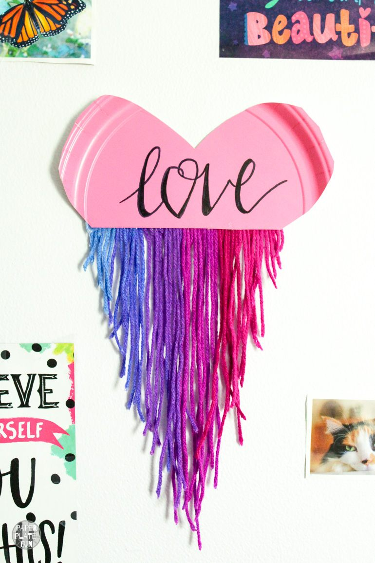 Teens and tweens will love this paper plate craft! Create a boho heart wall hanging with a paper plate and yarn!