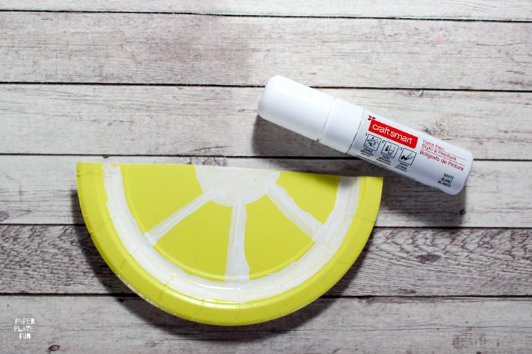 Use a white paint pen to create a paper plate lemon slice!