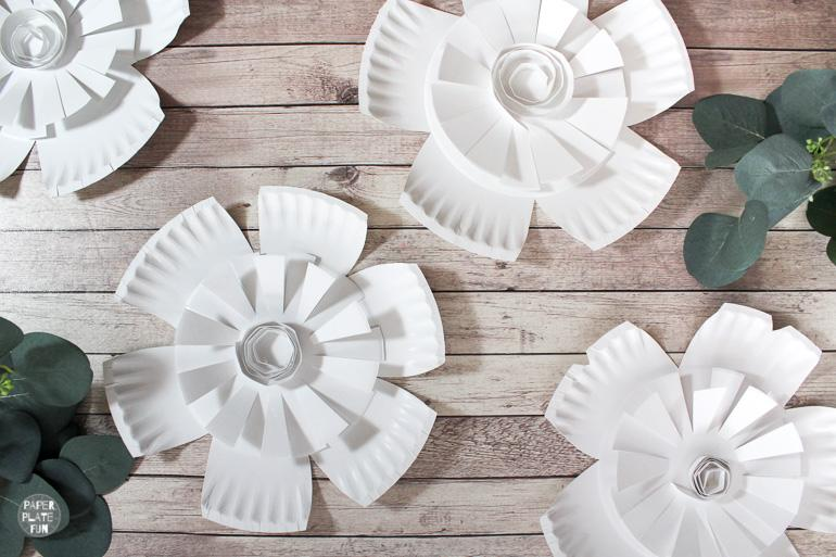 Create beautiful paper plate flowers with just two paper plates! These paper flowers are perfect for photo backdrops, paper plate wall decor, party decorations, and more!