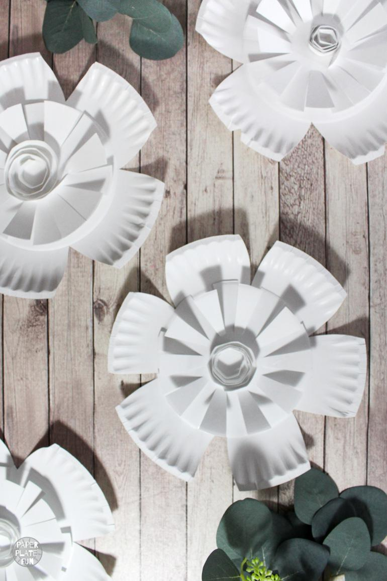 So cute! Learn how to make paper plate flowers for crafts and decor! These paper flowers are great for photo backdrops, party decor, dorm decor, and more.