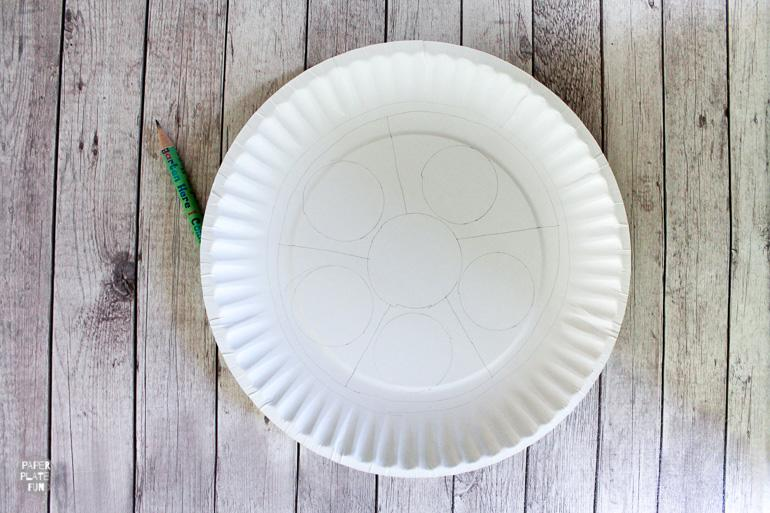 Draw a pattern on a paper plate to begin creating a mandala craft.